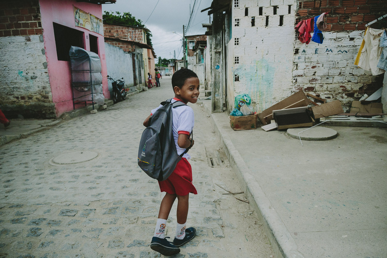 "After eating lunch and taking his shower and getting ready at his ""aunt's"" house (family friend---no relation), Emidio walks to his school."