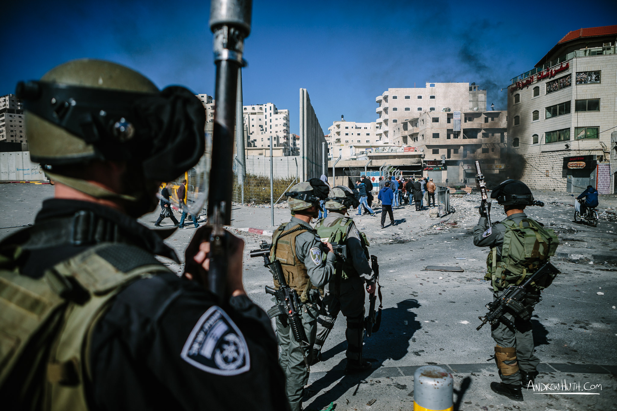 Israeli military using tear gas and guns in an armed conflict with the residents of Shu'afat Refugee Camp.  Palestinian youth clash with Israeli military in Shu'afat Refugee Camp in East Jerusalem on Friday, November 7, 2014. The recent, but temporarily total closure of one of Muslim's holiest sites, the Al-Aqsa Mosque, (the first since 1967) and the subsequent limited access for many Muslims to the mosque since has raised tension between Israeli's military and the Arab community.