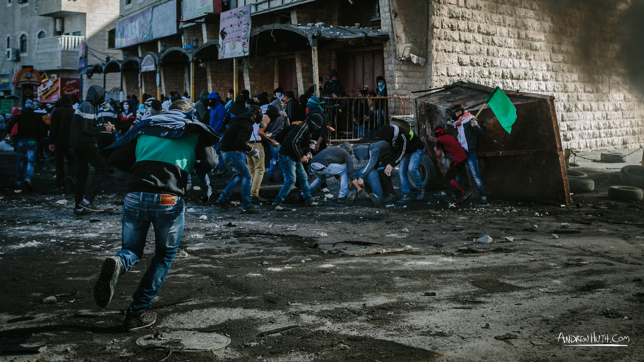 A Palestinian youth gets shot by Israeli military during a clash at Shu'afat Refugee Camp.  Palestinian youth clash with Israeli military in Shu'afat Refugee Camp in East Jerusalem on Friday, November 7, 2014. The recent, but temporarily total closure of one of Muslim's holiest sites, the Al-Aqsa Mosque, (the first since 1967) and the subsequent limited access for many Muslims to the mosque since has raised tension between Israeli's military and the Arab community.