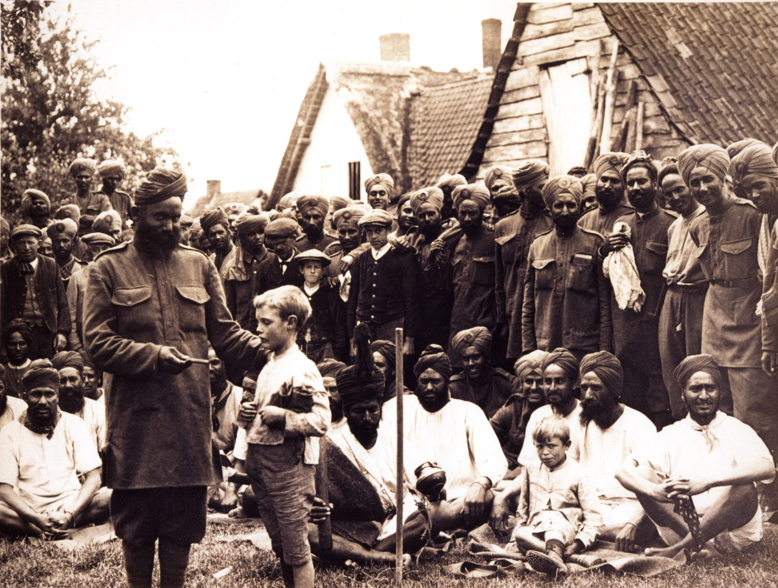 On Flanders Fields: Men of the 15th Sikh Regiment spend time with the locals in a Flanders village after weeks in the trenches of the Western Front, c. 1915. (Source: UKPHA Archive)