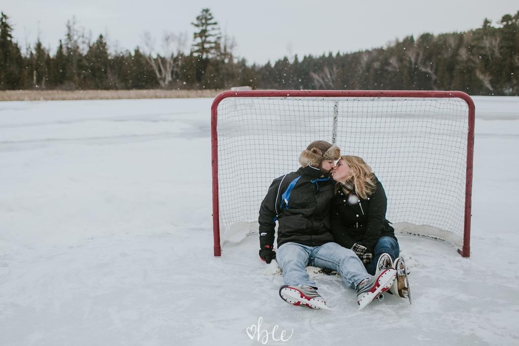 couple sitting under a hockey net on Palgrave Pond
