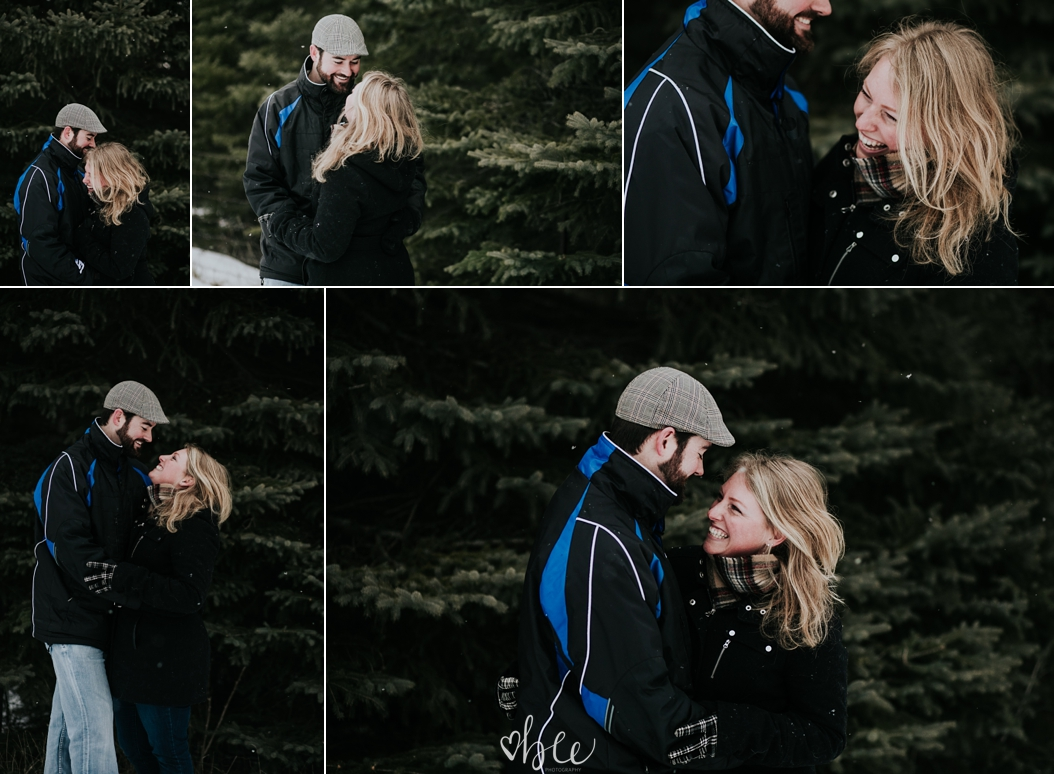 engaged couple snuggling outside in winter with dog