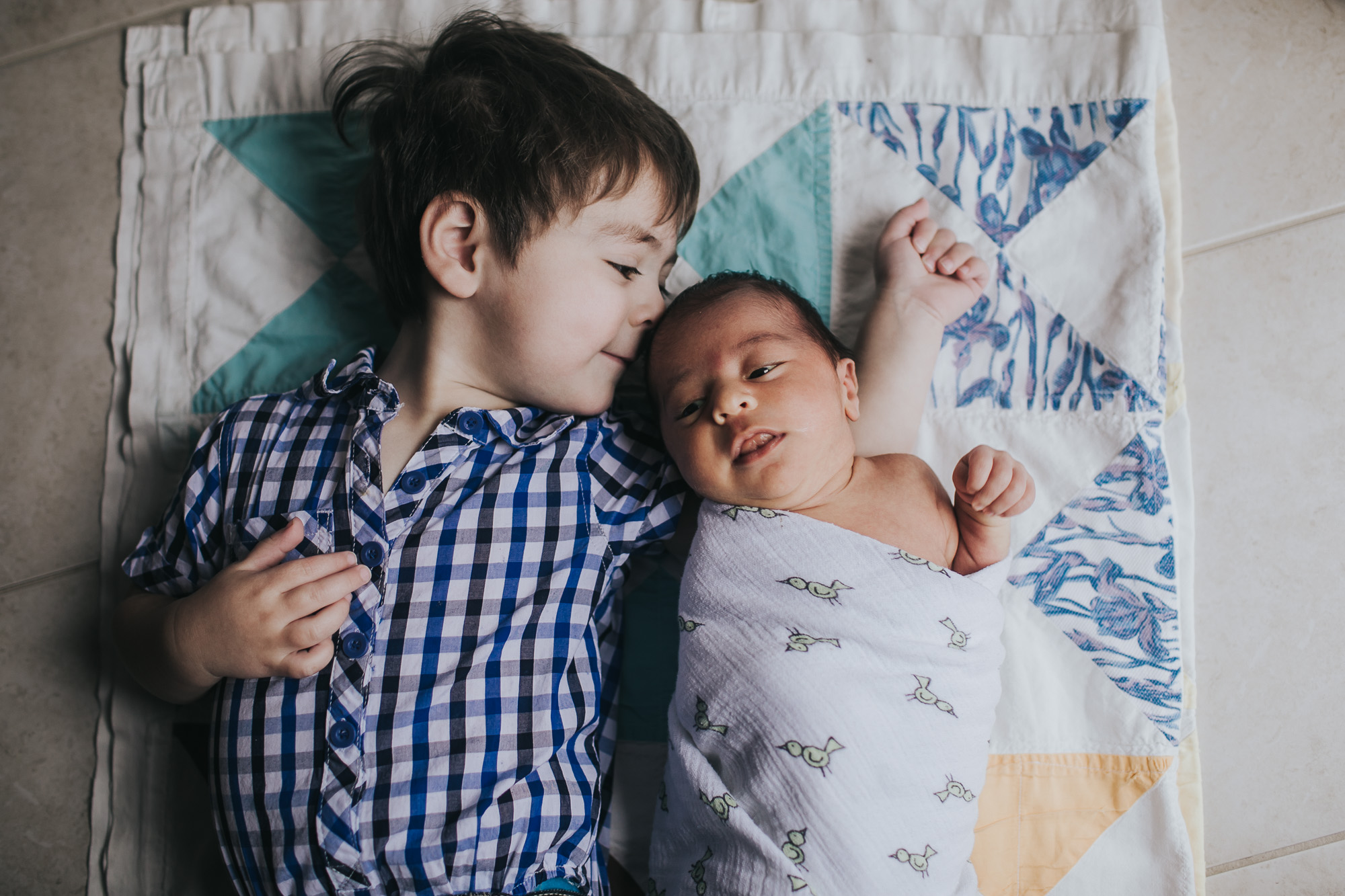 big brother laying with baby brother