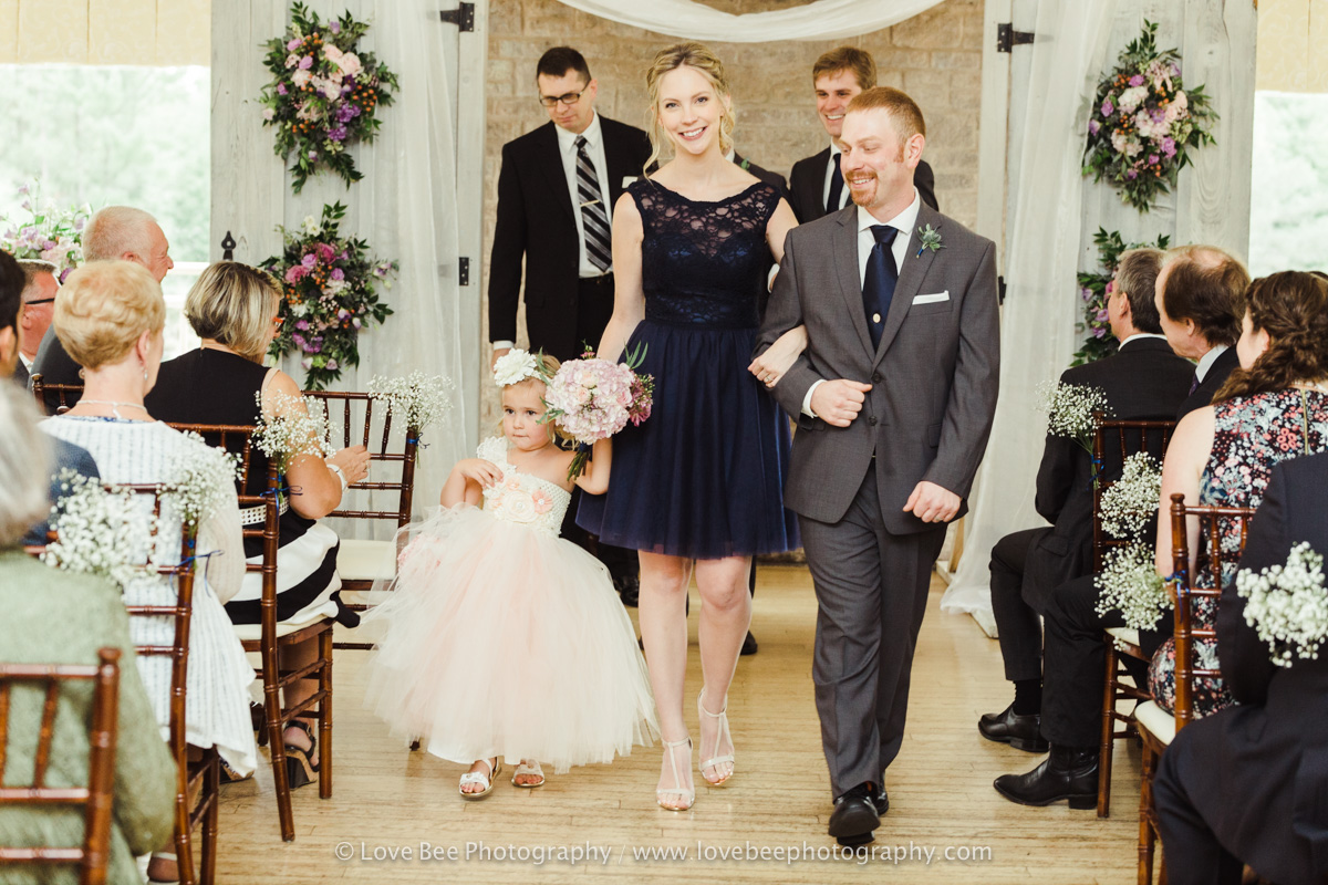 family with flower girl walking down aisle