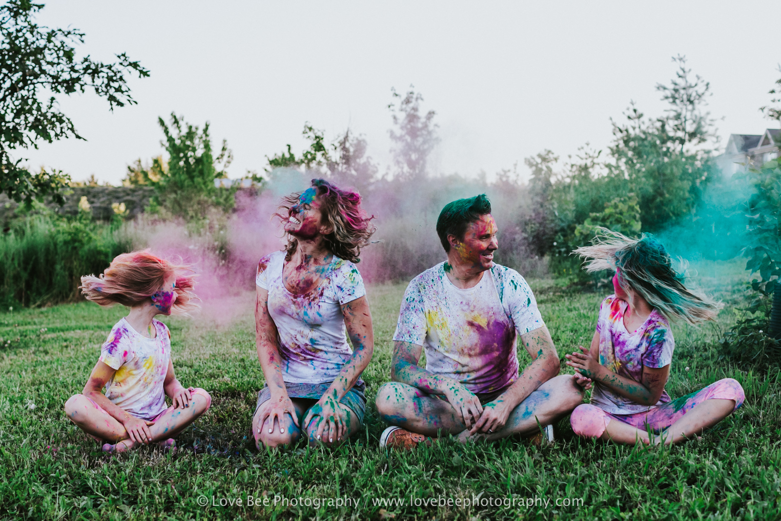family covered in holi coloured powder