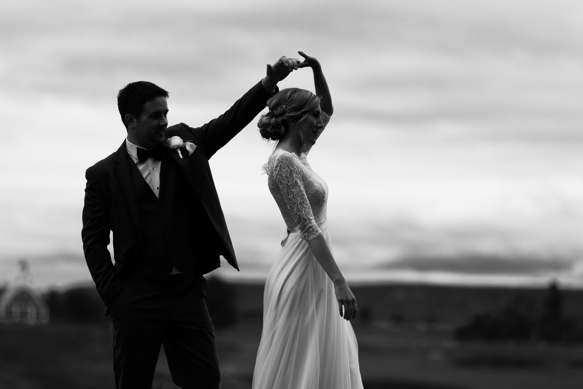 black and white image of a bride and groom dancing on a hill. Groom is spinning the bride