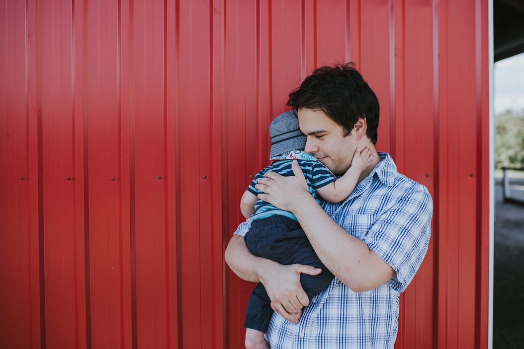 dad holding baby in front of a red wall at apple orchard in ontario canada
