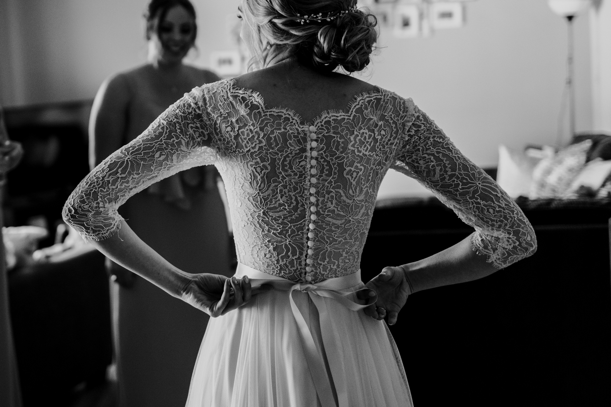 a bride is tying her dress with beautiful lace sleeves