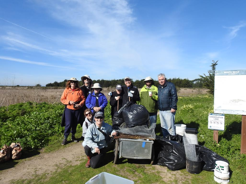 Volunteers celebrating a successful workday with the pile of trash pulled from the Wavecrest property.