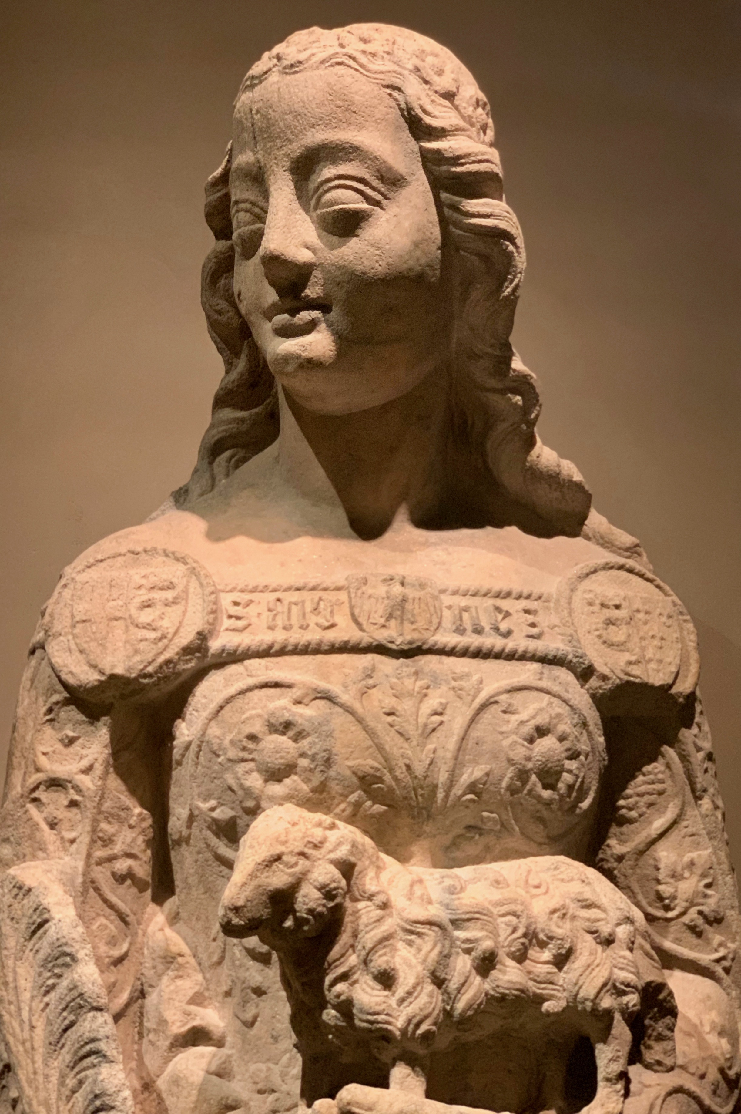 "This sculpture of St. Agnes from the second half of the 14th century by an unidentified artist was quite striking. It was observed in the Museum of the Milan Cathedral. Tradition tells us that, at age 12, Agnes was slighted for her religious devotion. Her declaration of a life of purity while being pursued by many suitors found her being punished for such by being dragged naked in the streets to be placed in a brothel. She turned to days of prayer in the midst of this unfavorable environment. Tragically Agnes was ultimately killed for her steadfastness and virginity.   Inspiration take away  —gain strength from the stories of faith of those who have gone before us. Also admiration for how the artist used the many symbols in this ""simple"" sculpture … do you see the shields, the lily, the roses, the lamb, the grapes and vines?"