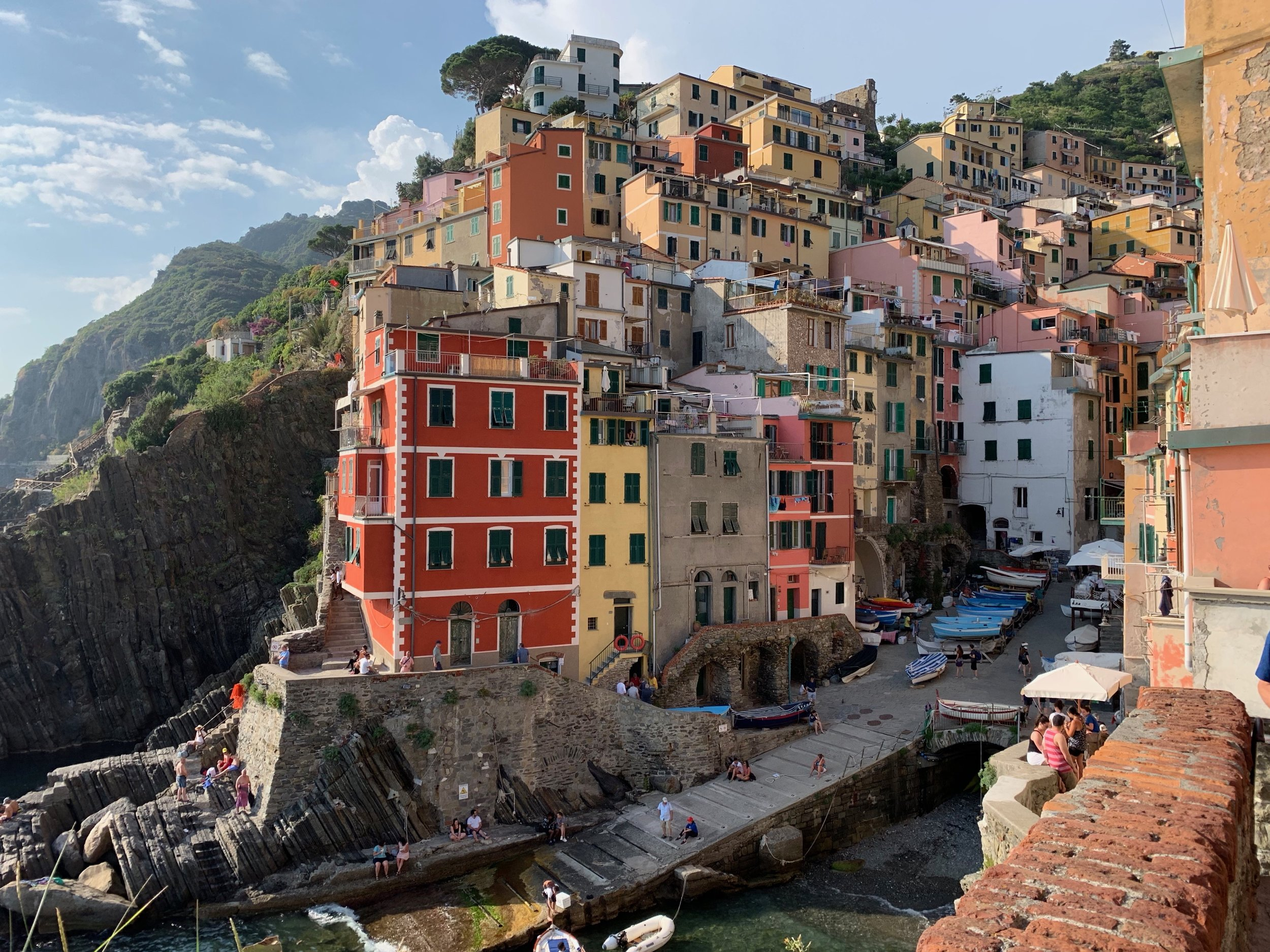 Cinque Terre is a string of centuries old seaside villages on the rugged Italian Riviera coastline. Each of the towns is built around the valley harbor and is filled with colorful buildings surrounded by terraced vineyards and farm land. Hiking from village to village going up one mountain and then down the next gave us sweeping vistas. This is the town of Riomaggiore.   Inspiration take away  — The colors, the community, and highly regarding the hard work of the fishing and farming industries in this area.