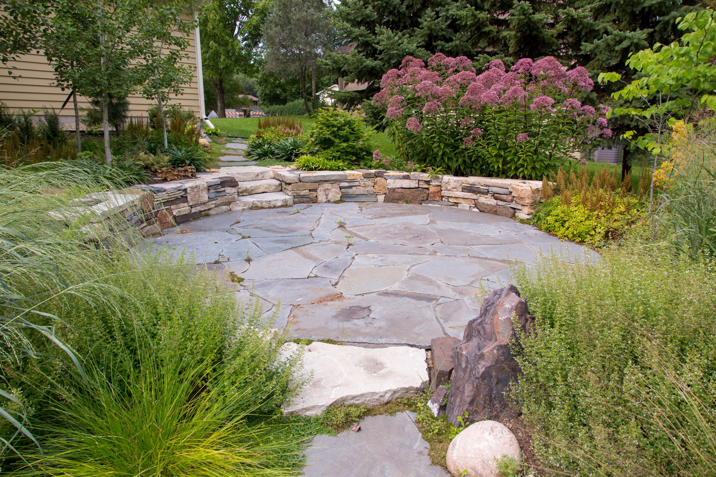 After: Phillips' custom stone sitting wall and lush prairie-style plantings frame a cozy patio.