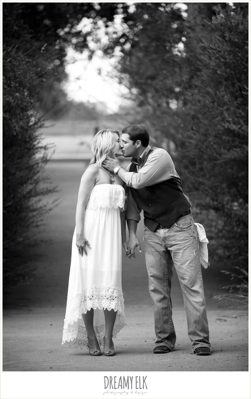romantic outdoor engagement photo, jeans and vest, white dress, couple kissing