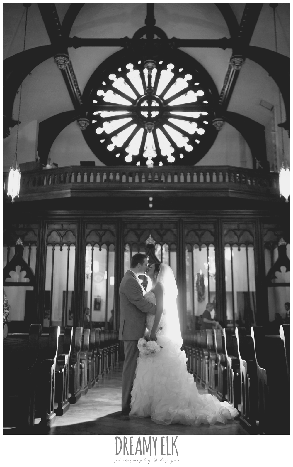 bride and groom kissing in church aisle, st mary's cathedral, downtown austin spring wedding {dreamy elk photography and design}