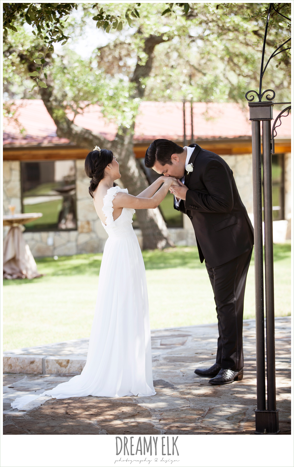 bride and groom seeing each other before the wedding, first look, groom kissing bride on the hand, chiffon wedding dress with ruffle sleeve, la hacienda, dripping springs, texas {dreamy elk photography and design} photo