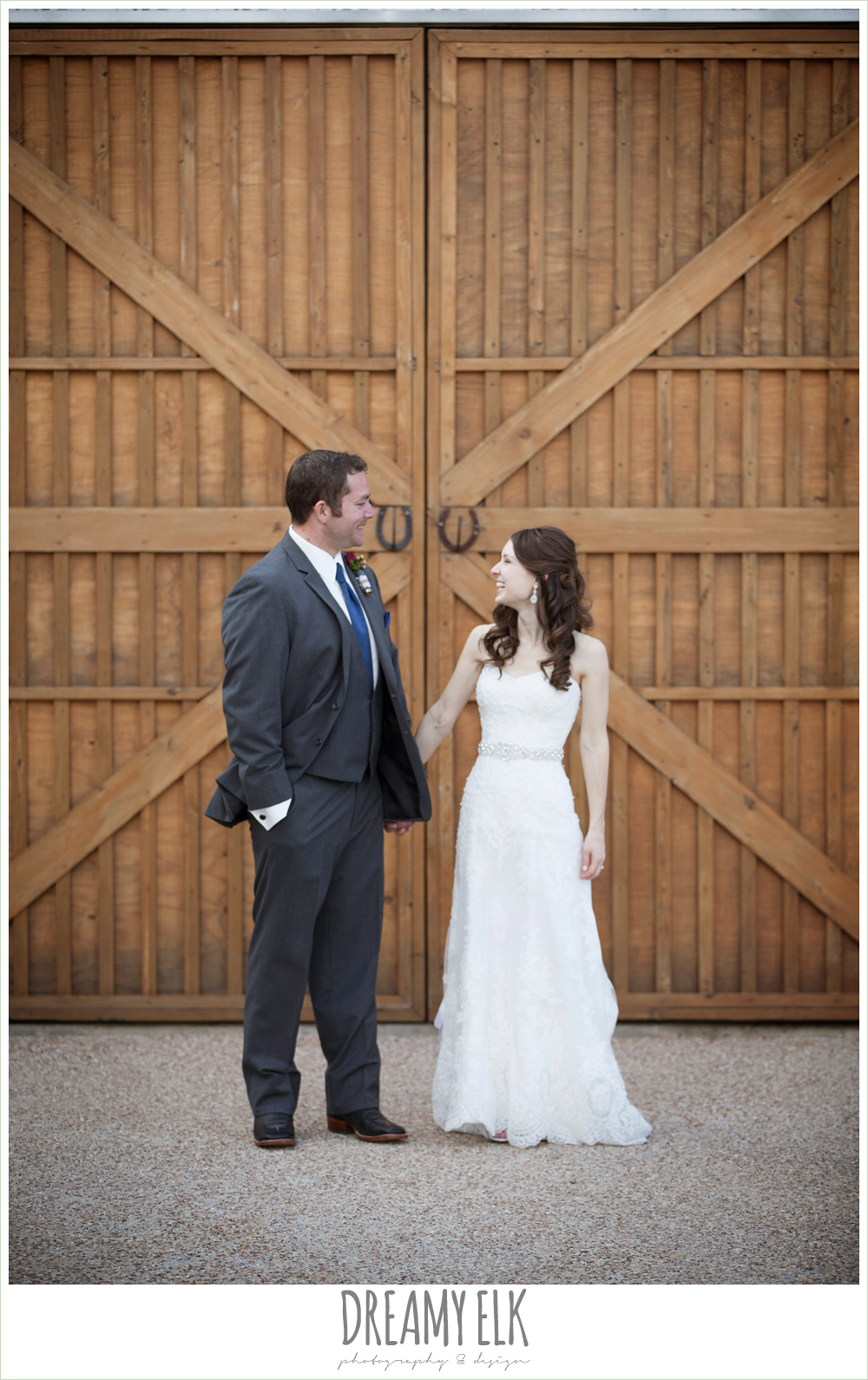 bride and groom laughing in front of a barn door, strapless lace wedding dress with belt, gray suit and navy tie, pine lake ranch, rustic wedding photo {dreamy elk photography and design}