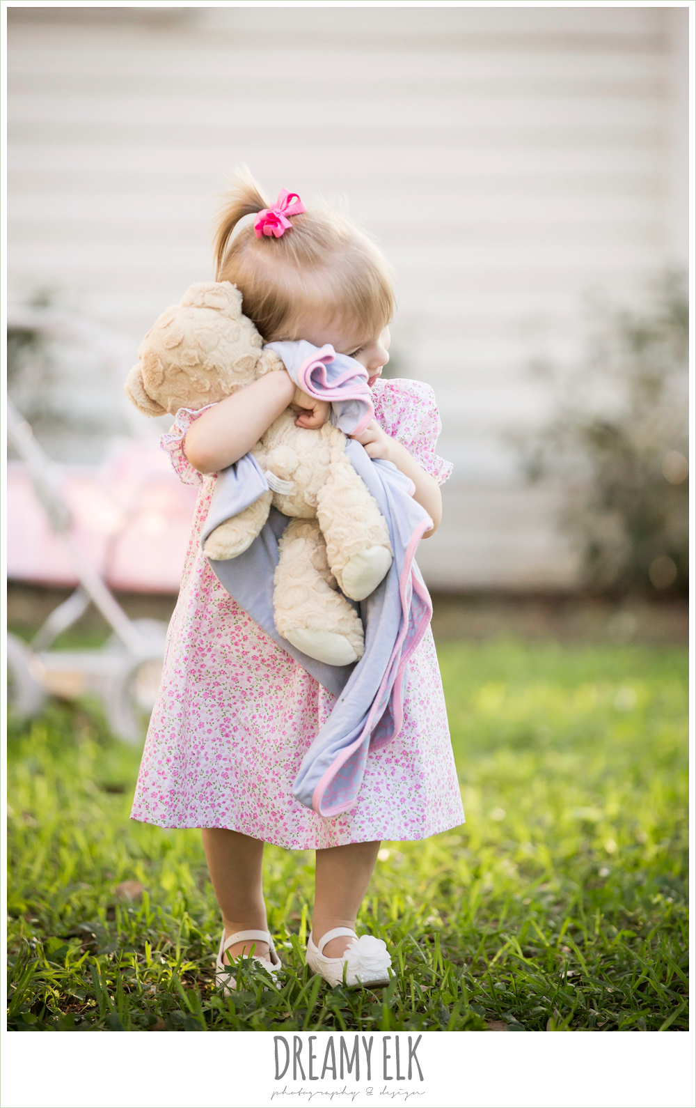 18 month old photo, photo of girl toddler outside with pottery barn doll pram and stuffed teddy bear