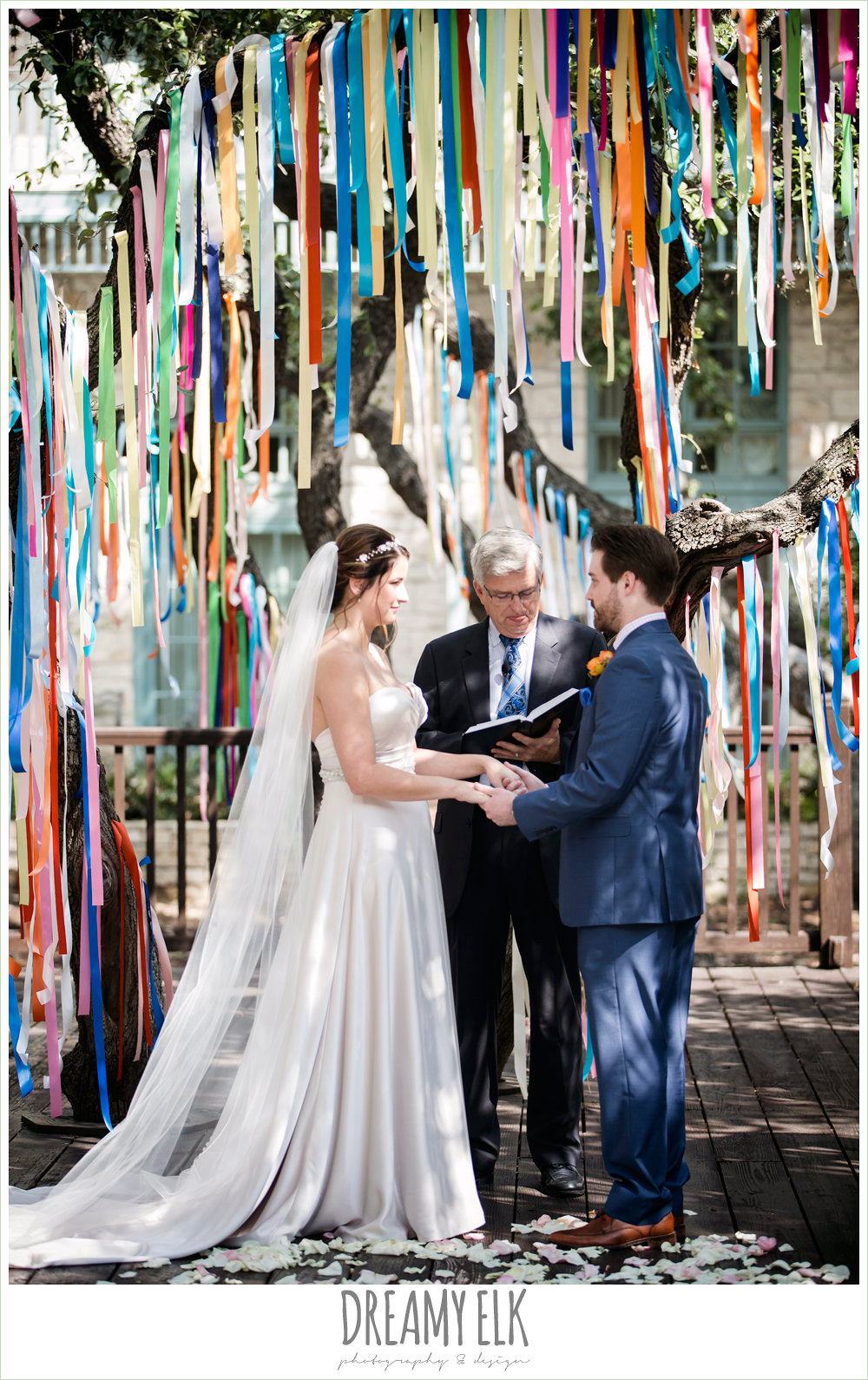 colorful streamers in trees ceremony decorations, groom in men's wearhouse navy suit pink shirt and navy tie, sweetheart strapless justin alexander wedding dress in sand color, bride and groom during ceremony, colorful outdoor sunday morning brunch wedding, hyatt hill country club, san antonio wedding photo {dreamy elk photography and design}