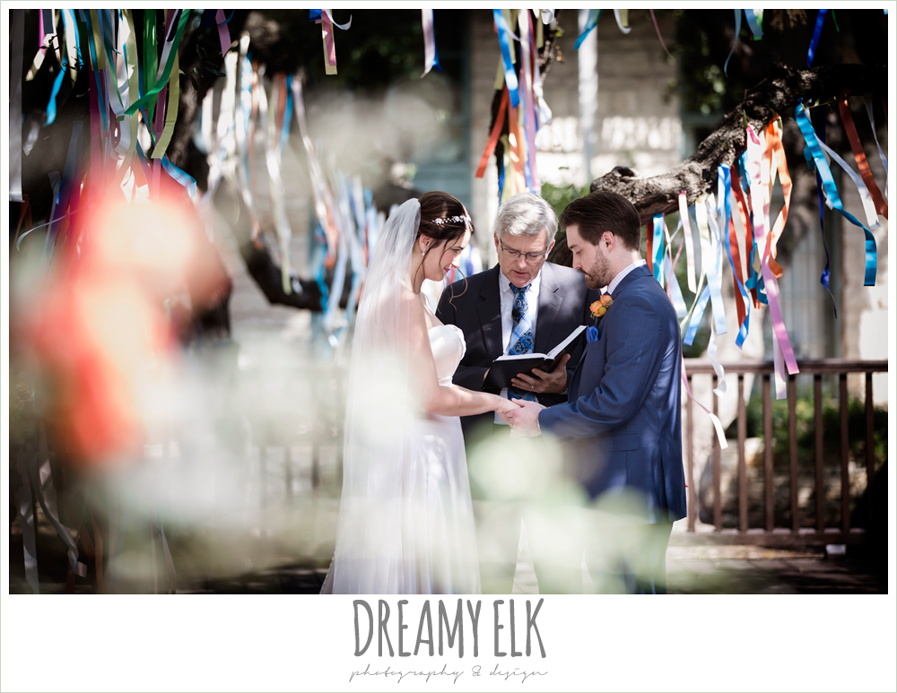 colorful streamers in trees ceremony decorations, sweetheart strapless justin alexander wedding dress in sand color, bride and groom during ceremony, colorful outdoor sunday morning brunch wedding, hyatt hill country club, san antonio wedding photo {dreamy elk photography and design}