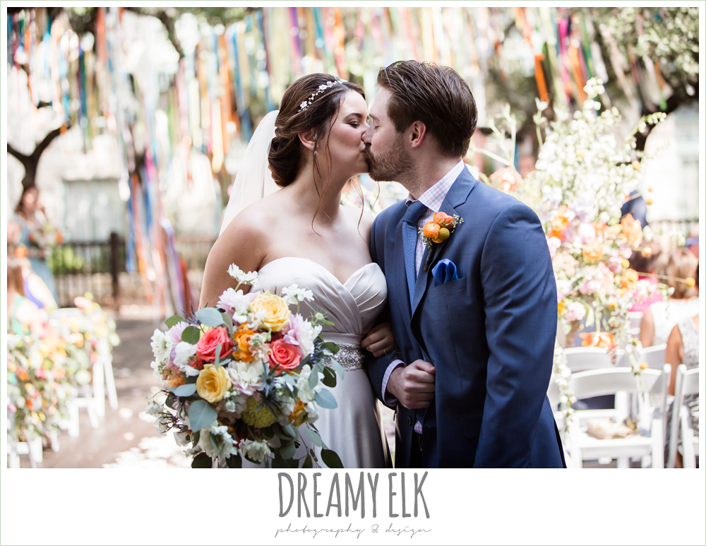 colorful streamers in trees ceremony decorations, Plans n' Petals wedding bouquet, groom in men's wearhouse navy suit pink shirt and navy tie, bride and groom kissing during ceremony, colorful outdoor sunday morning brunch wedding, hyatt hill country club, san antonio wedding photo {dreamy elk photography and design}sweetheart strapless justin alexander wedding dress in sand color,