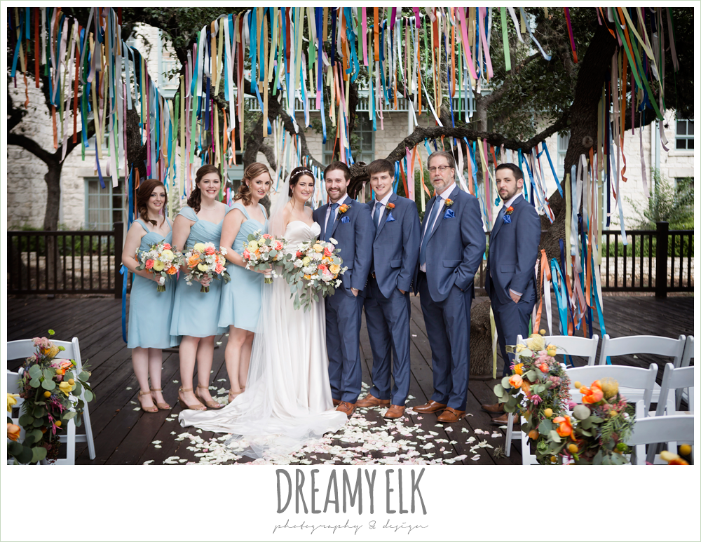 colorful streamers in trees ceremony decorations, Plans n' Petals wedding bouquet, groom in men's wearhouse navy suit pink shirt and navy tie, bill levkoff bridesmaid dress in glacier blue, sweetheart strapless justin alexander wedding dress in sand color, bridal party, colorful outdoor sunday morning brunch wedding, hyatt hill country club, san antonio wedding photo {dreamy elk photography and design}