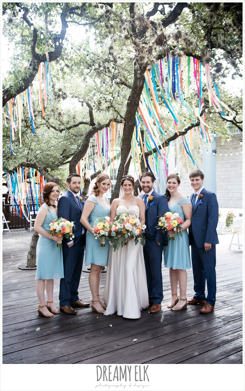 colorful streamers in trees ceremony decorations, groom in men's wearhouse navy suit pink shirt and navy tie, bill levkoff bridesmaid dress in glacier blue, sweetheart strapless justin alexander wedding dress in sand color, bridal party, colorful outdoor sunday morning brunch wedding, hyatt hill country club, san antonio wedding photo {dreamy elk photography and design}