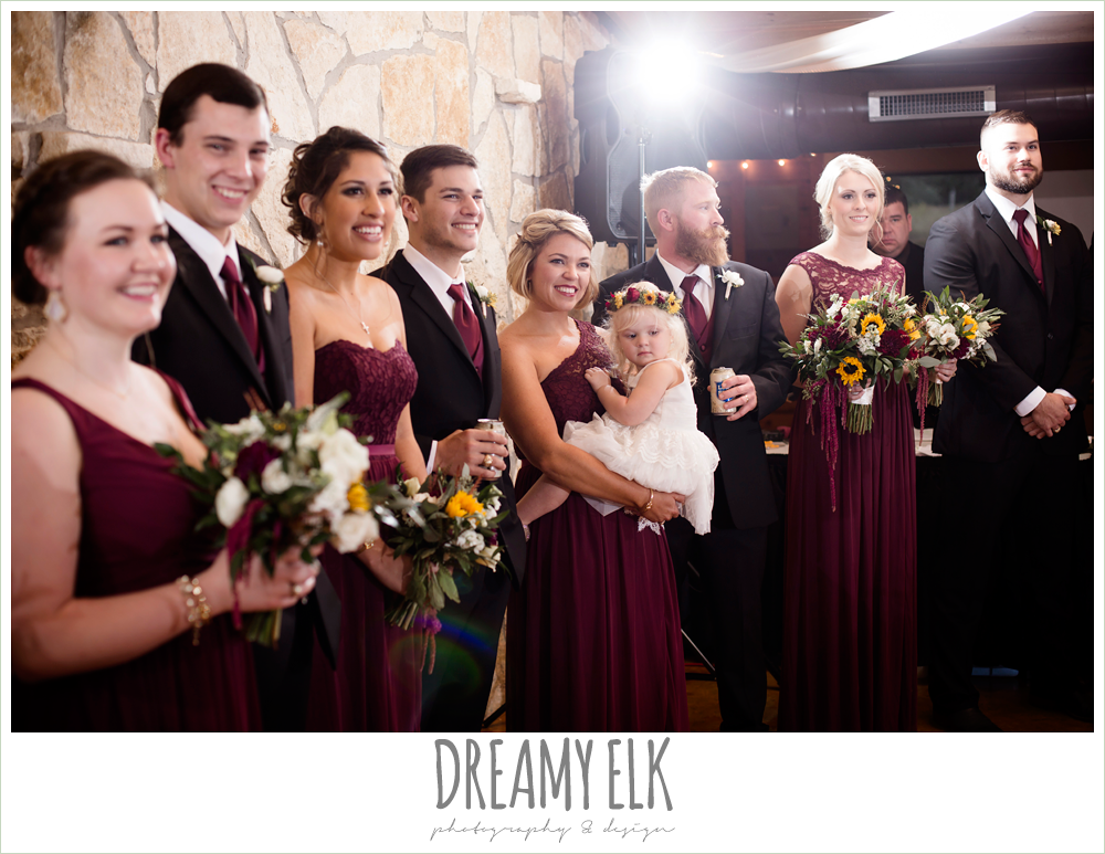 mix and match maroon long chiffon bridesmaid dresses, david's bridal, wild bunches floral, bridal party watching bride and groom dance, indoor wedding reception, maroon and gold fall wedding photo, la hacienda, dripping springs, texas {dreamy elk photography and design}