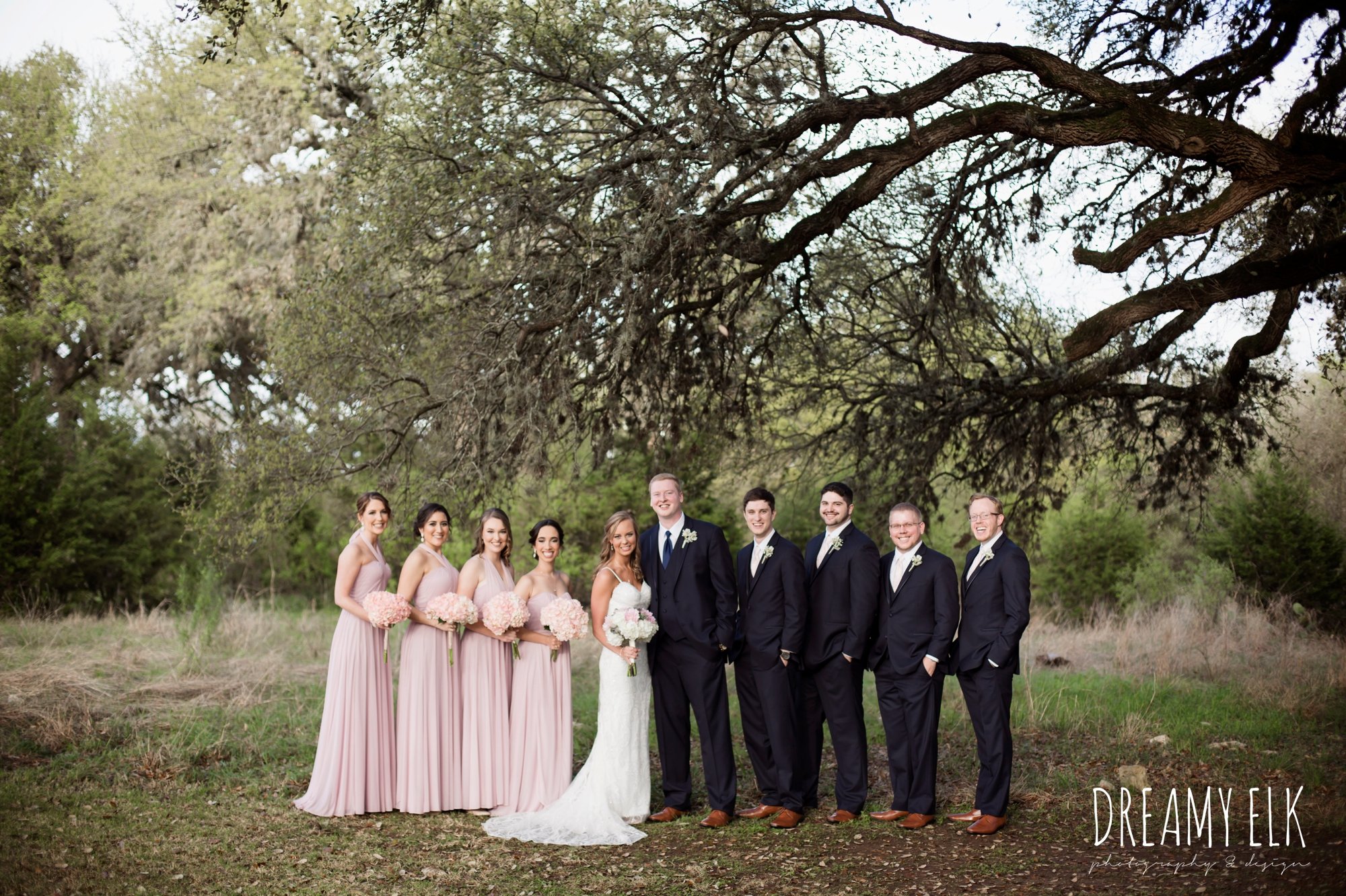 groom and groomsmen in navy suits, bride and bridesmaids, mix and matched floor length blush bridesmaid dresses, backless column sheath wedding dress, cloudy march wedding photo, canyon springs golf club wedding, san antonio, texas {dreamy elk photography and design}