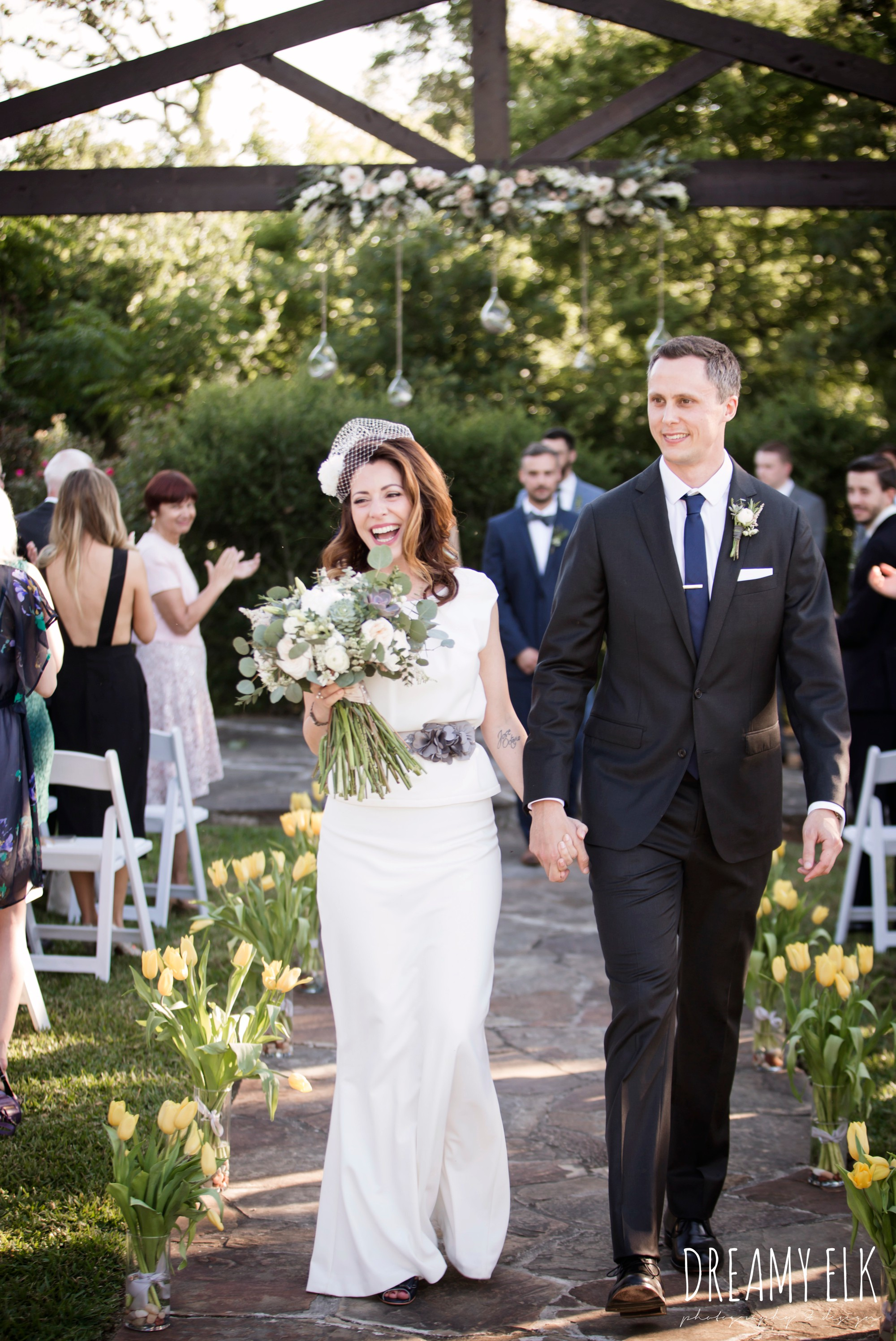 bride and groom walking down the aisle, unforgettable floral, white and green succulent wedding bouquet, bride, handmade wedding dress, two piece wedding dress, gray sash, bird cage veil, outdoor april spring wedding photo, double creek crossing, college station, texas, austin wedding photographer {dreamy elk photography and design}