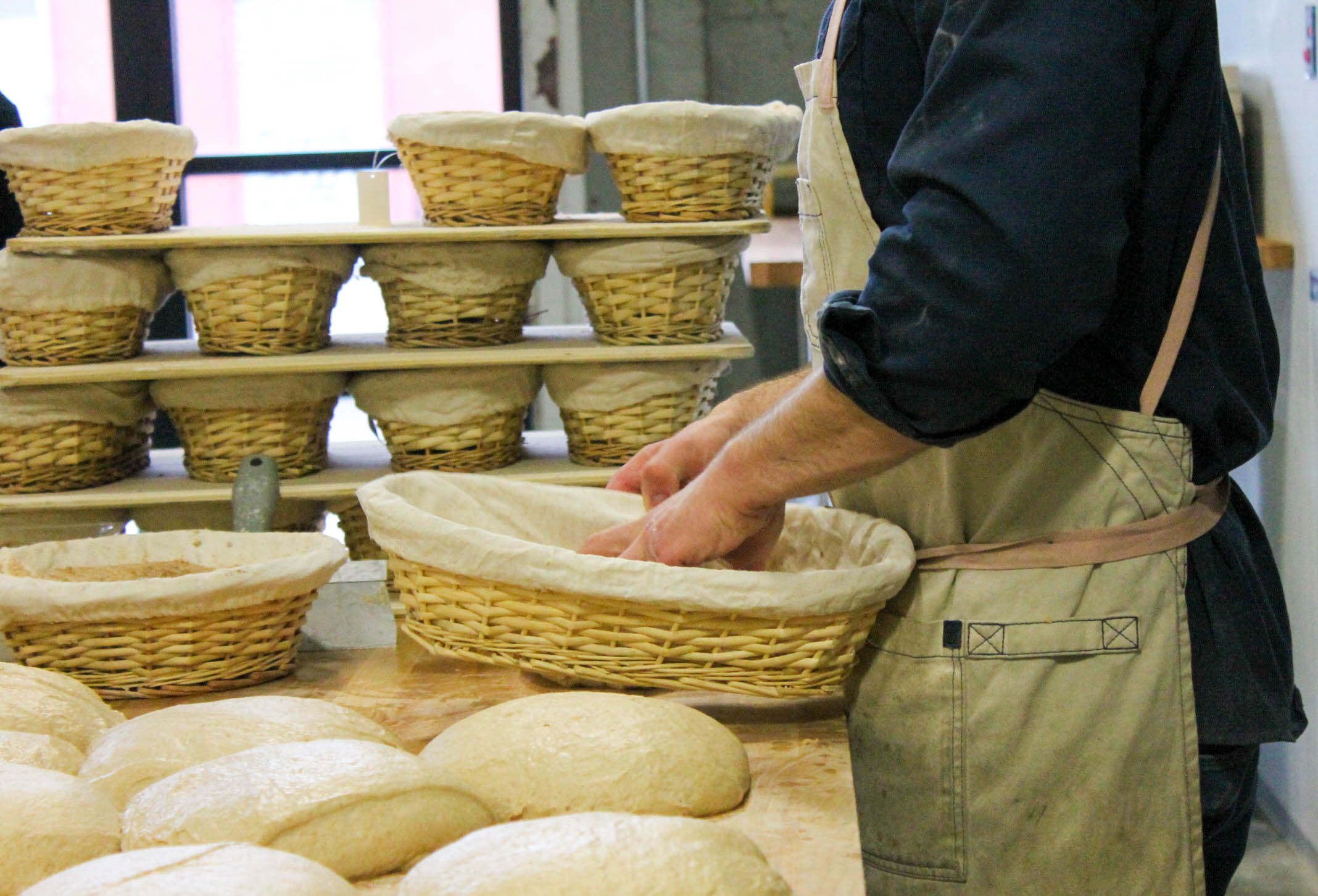 Flouring the proofing baskets.