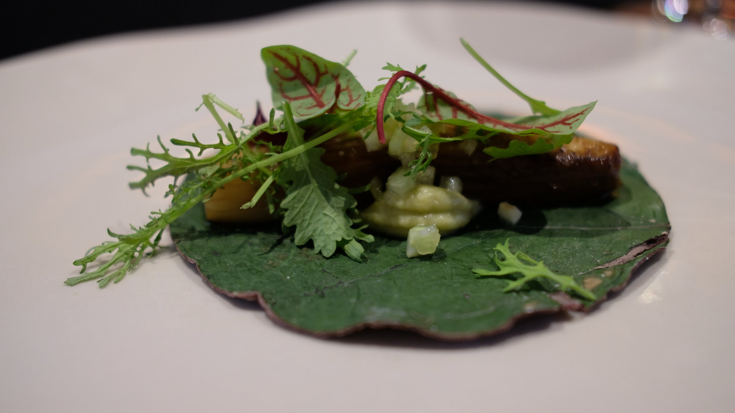 Eggplant taco with hoja santa and green pico de gallo on a blue corn tortilla