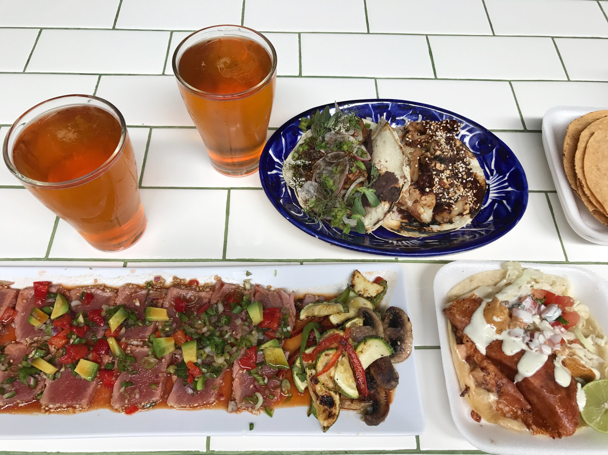 Draft pours from Cervecería Insurgente beer with tacos from La Camelita and raw tuna from a vendor at Telefónica Gastro Park.