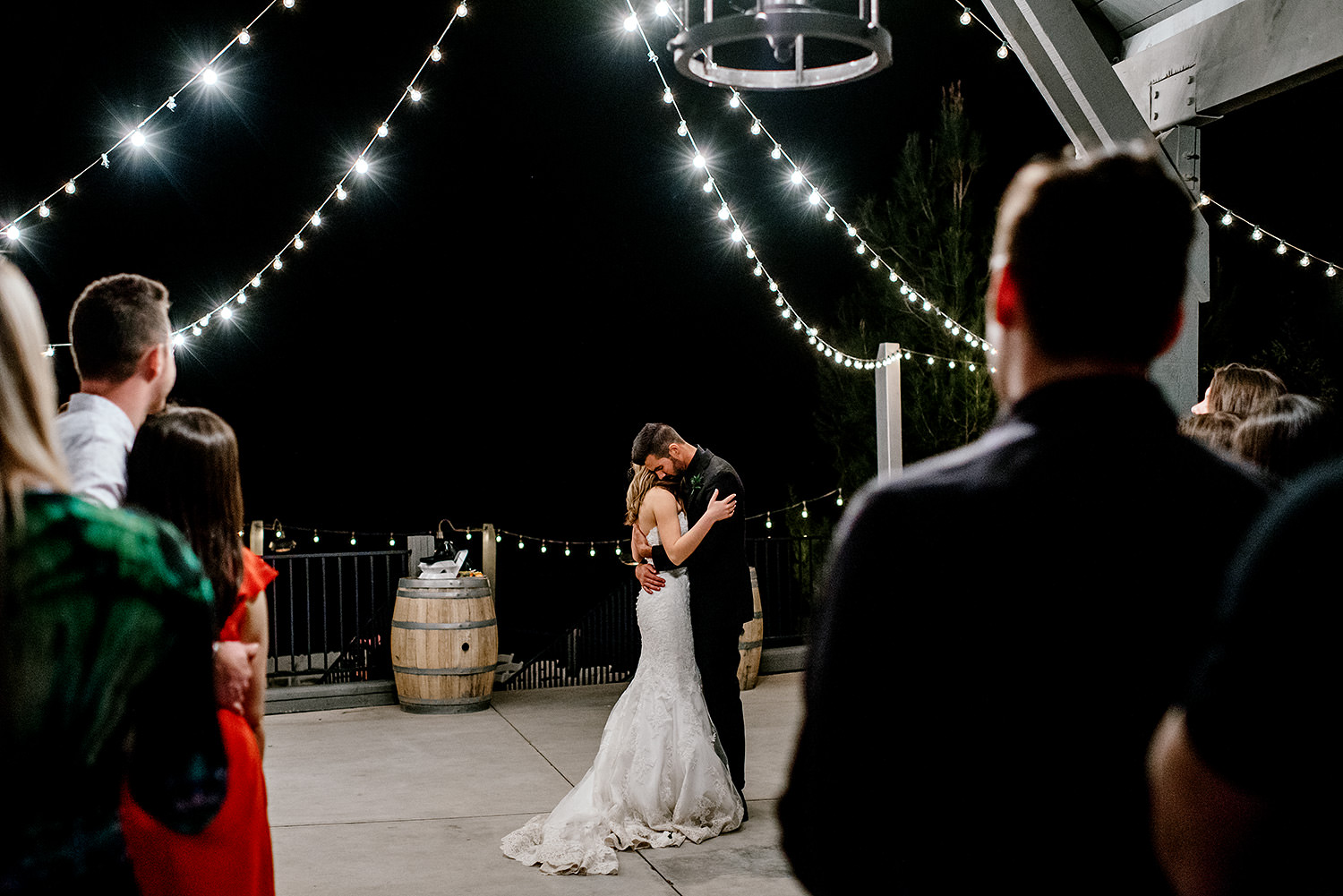 bride and groom first dance under string lights