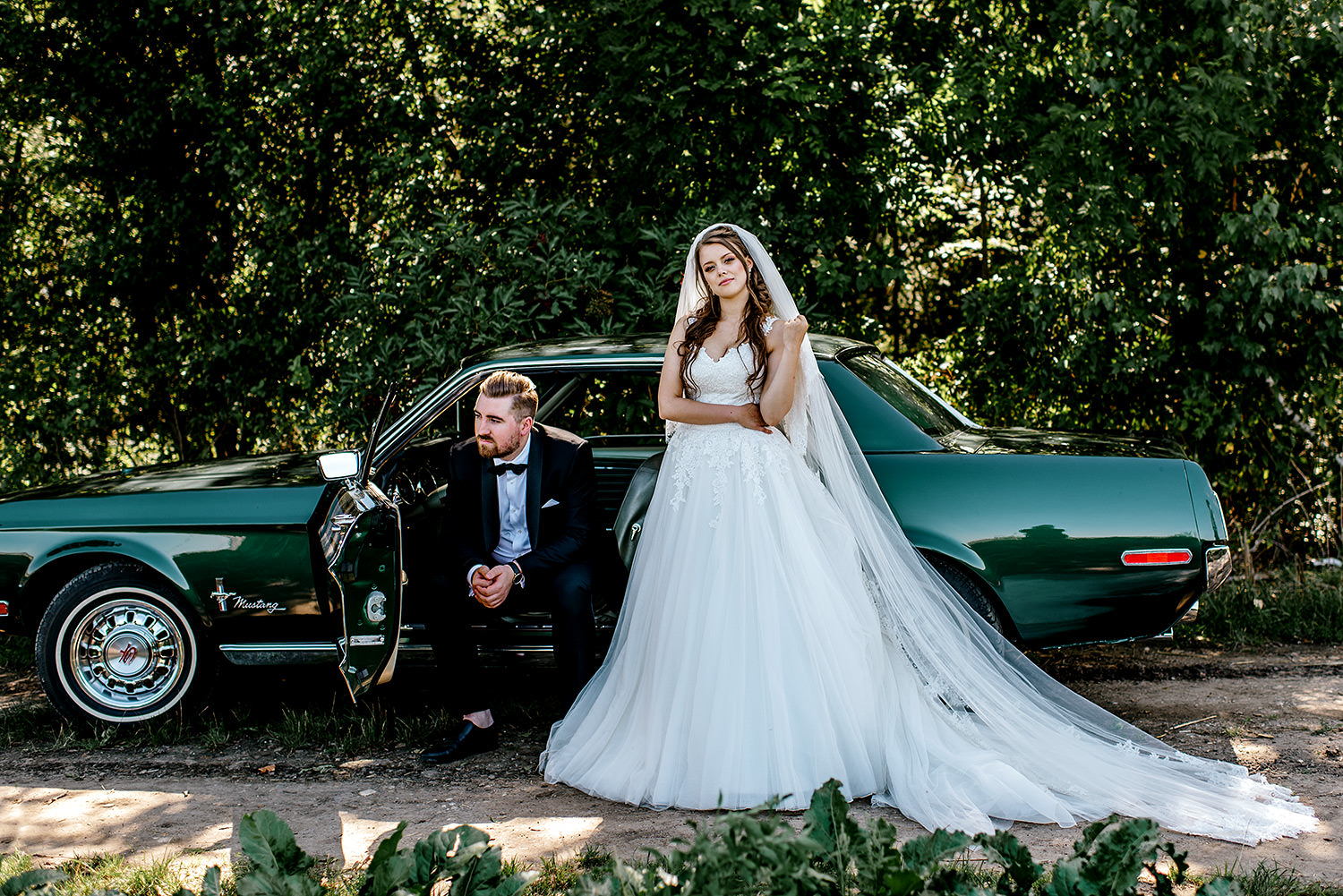 bride and groom standing by wedding car