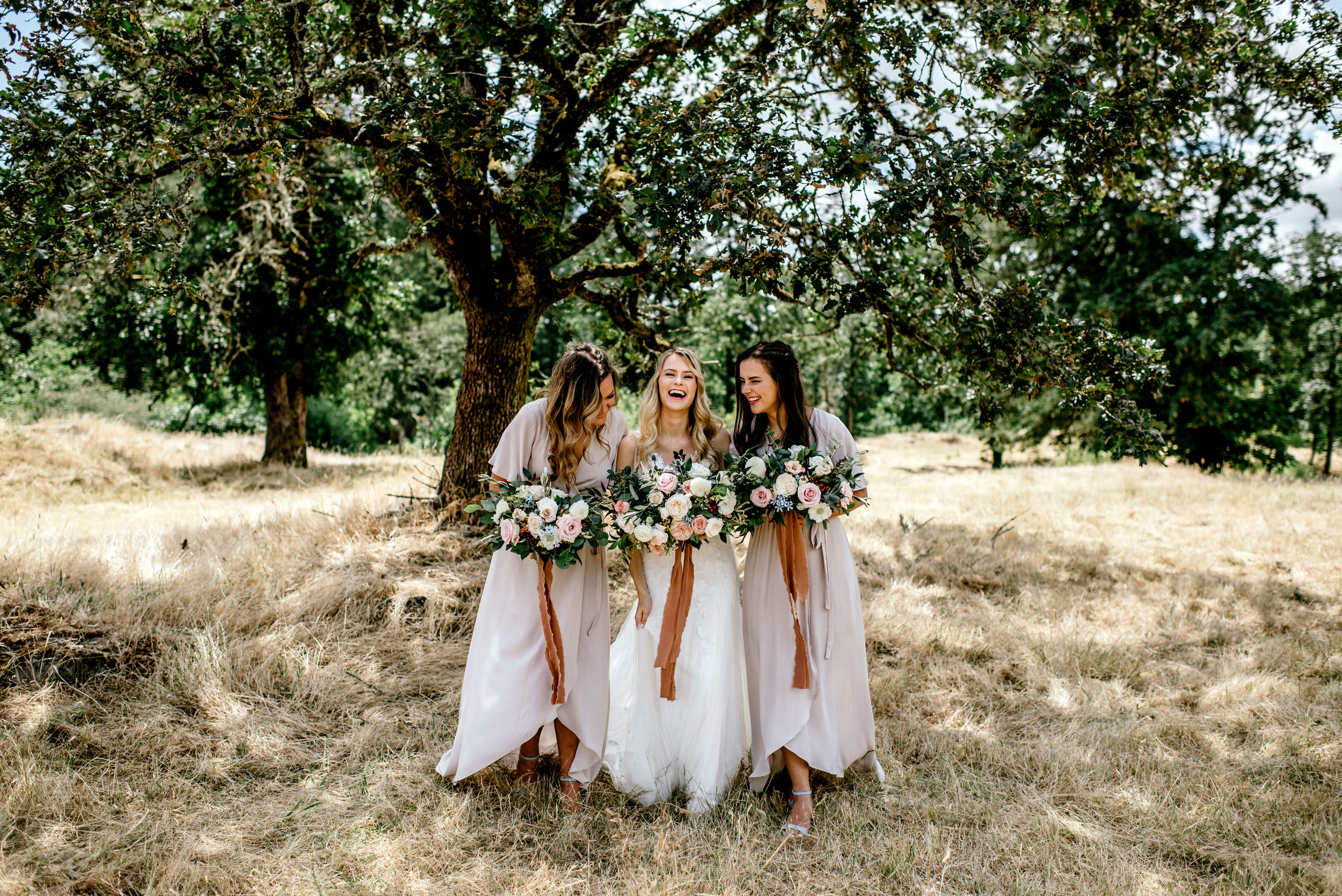 bride and her  bridesmaids walking together in a field