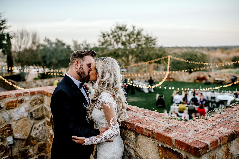Bride and groom sharing a kiss overlooking the wedding reception at Bella Collina Florida