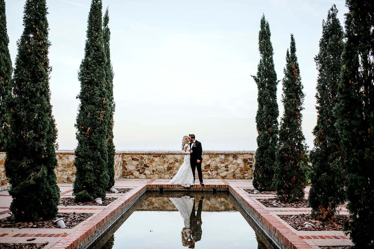 Bride and groom kissing in front of beautiful pool outlined with tall spartan juniper trees at Bella Collina Florida.