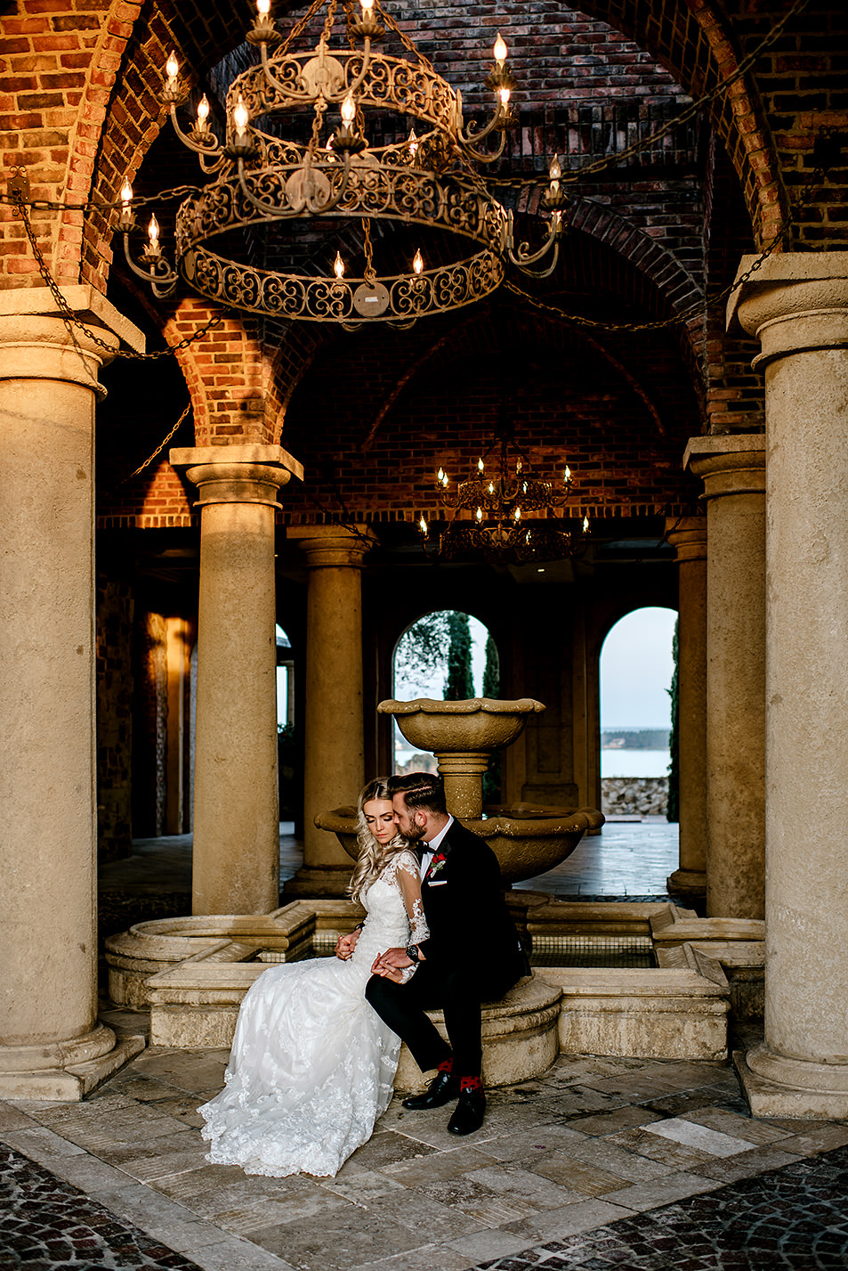 Portrait of bride and groom sitting by a water fountain at Bella Collina Florida, during sunset.