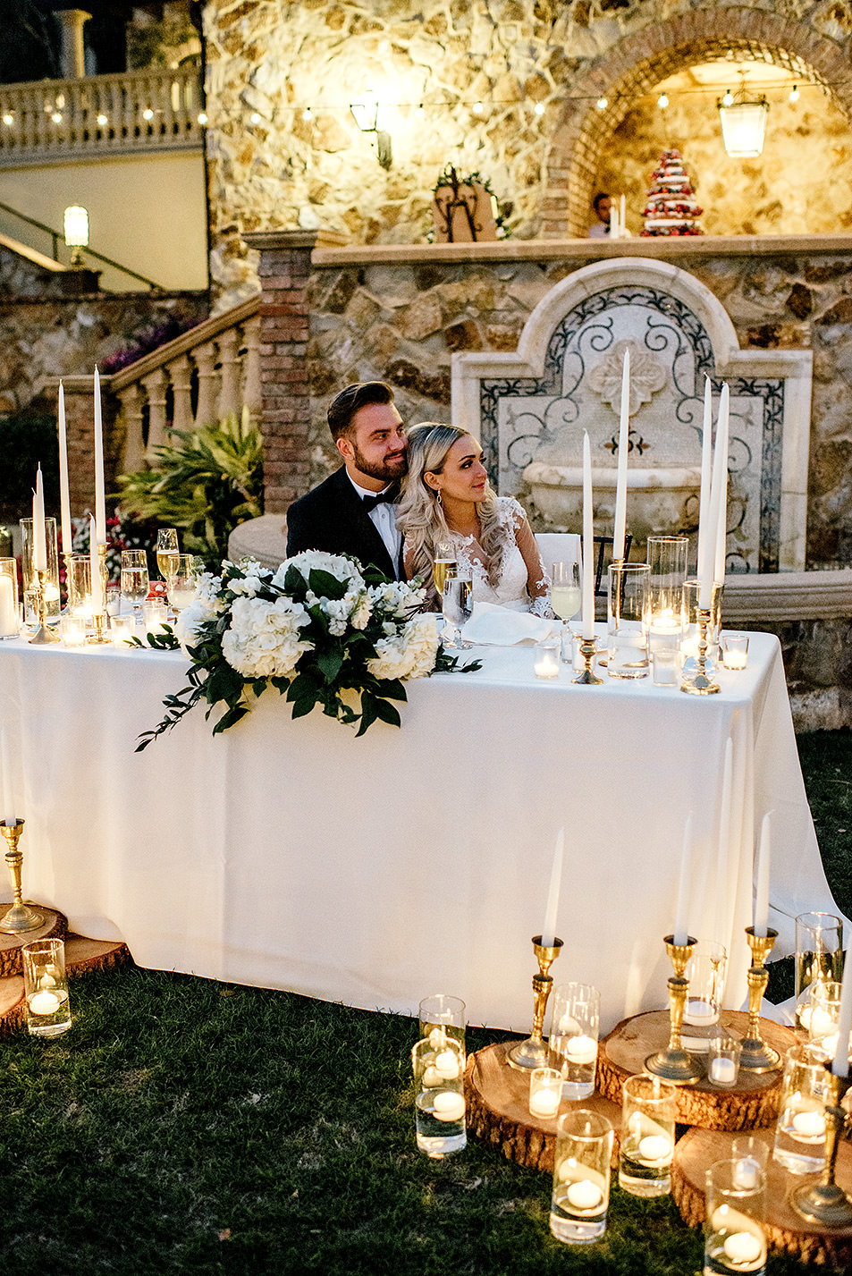Bride and groom sitting at their candle filled sweetheart table during their reception at Bella Collina Florida