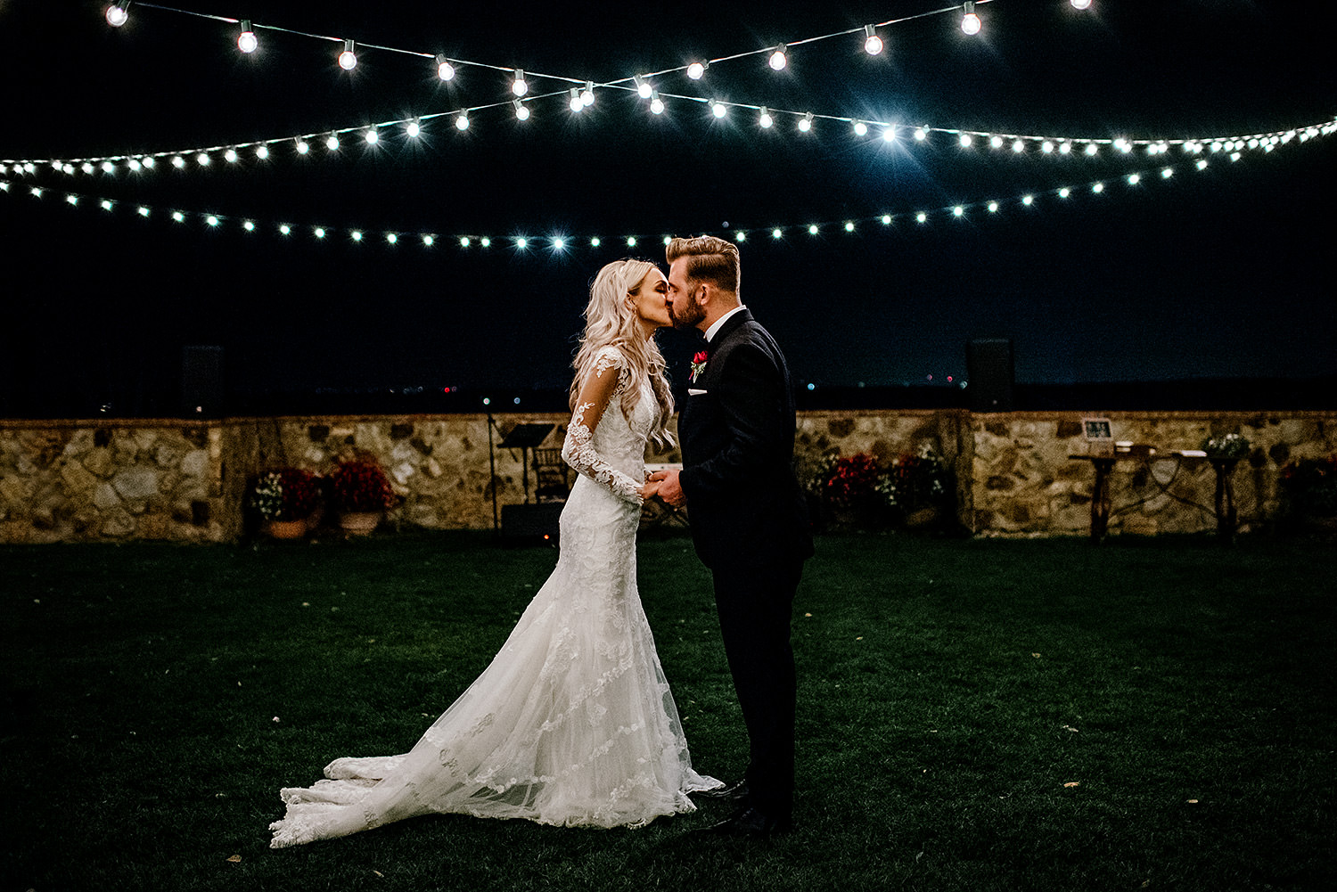 A night time portrait of a bride and groom kissing under hanging string lights at Bella Collina Florida