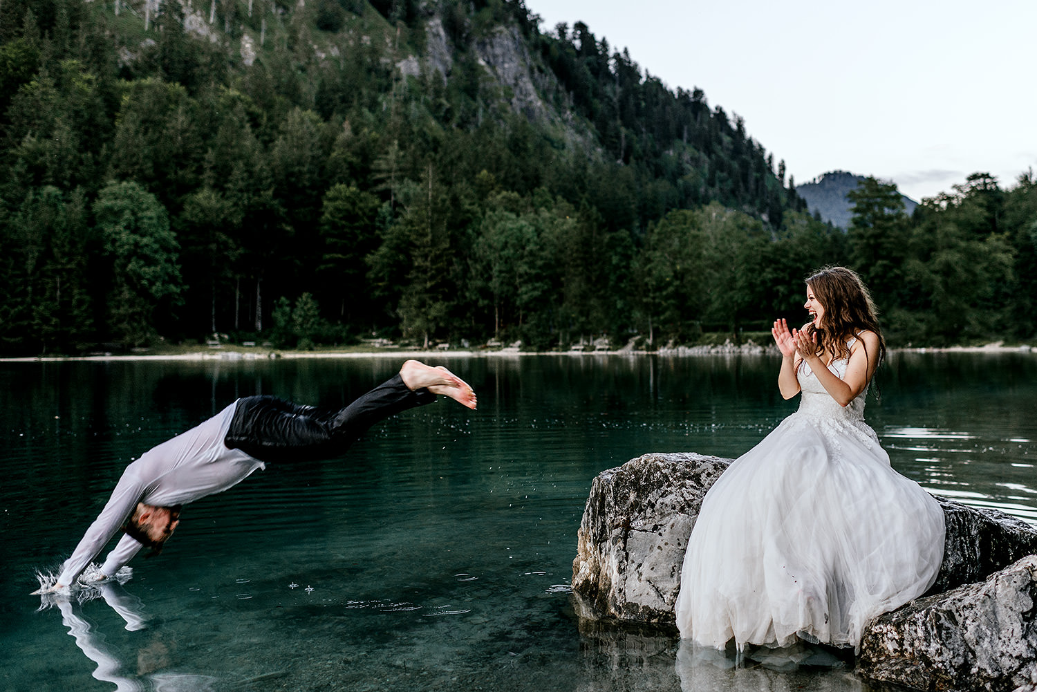 bride and groom jumping into the lake
