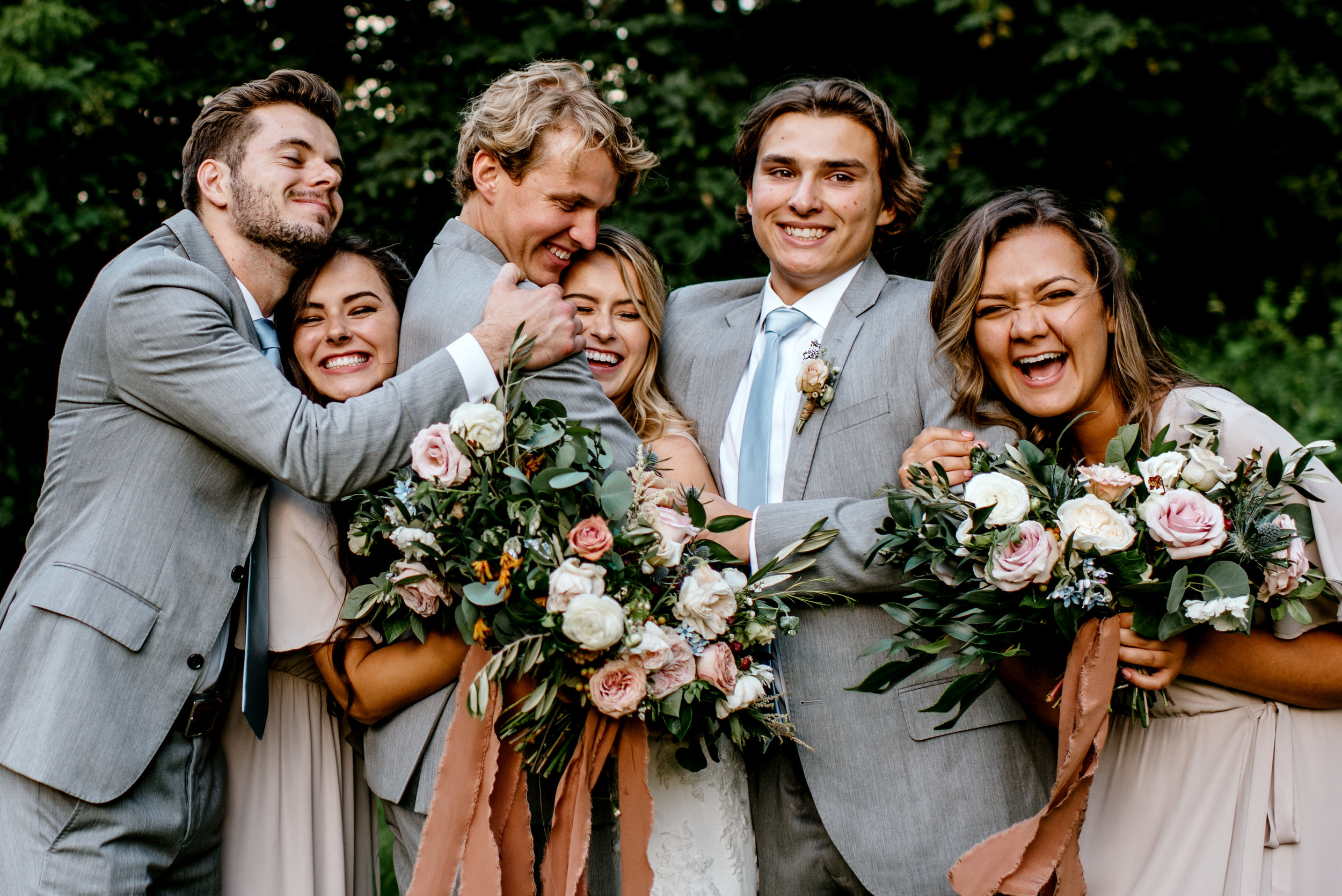 bridal party group hug with bride and groom