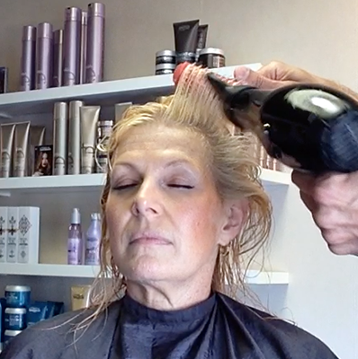 Step 1: Using the Denman D31 detangling brush, I begin in front of the ear and pick up hair along the hairline while blowing drying as I lift the brush out, up, and away, straight off the frame of the face. I continue this along the hairline and complete on the other side of the face. The benefit of this is literally creating a lift off the face and creating an impactful frame with the hair.
