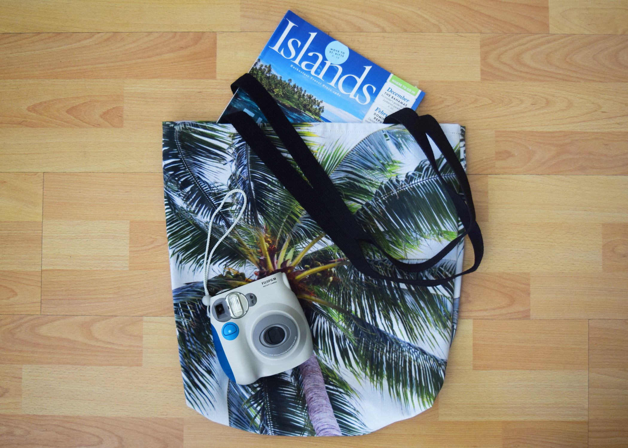 caribbean palm tote on floor with magazines and instax camera.jpg