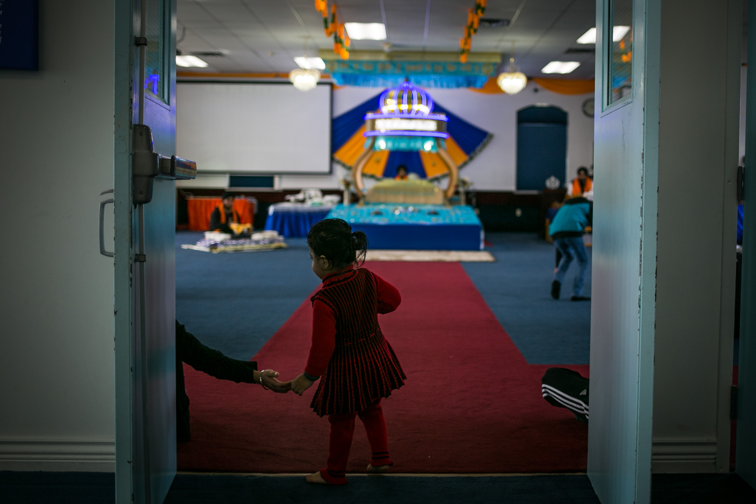 A child enters the Darbar Sahib, the main prayer hall, of Sikh temple Guru Nanak Gursikh Gurudwara in Lynden, Washington during a prayer service on March 1, 2015. During Sikh prayer services, participants sit barefoot on the floor of the the prayer hall after prostrating before the Sikh sacred text upon entering the room.
