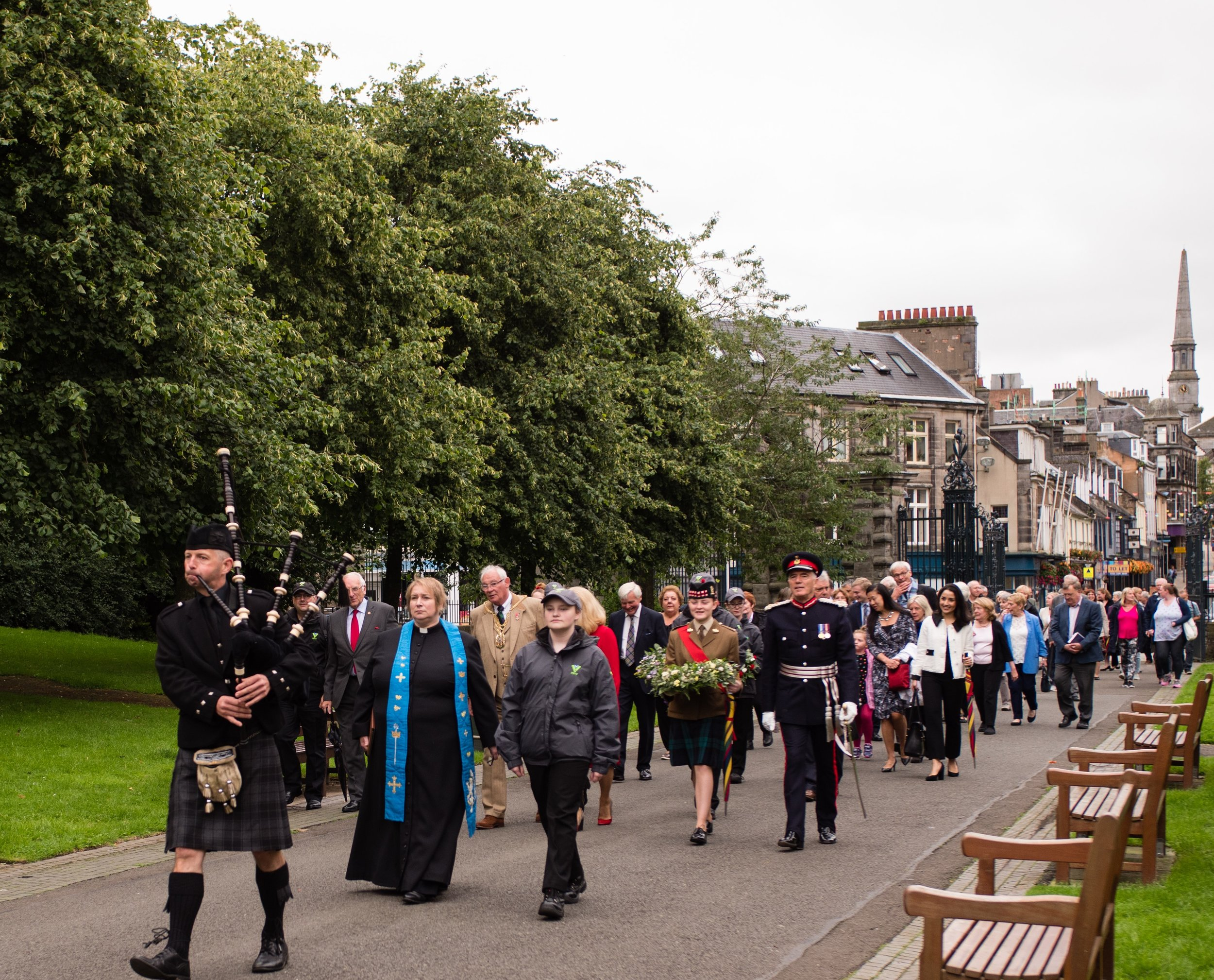 The piper leading the procession to Andrew Carnegie's statue in Pittencrieff Park.