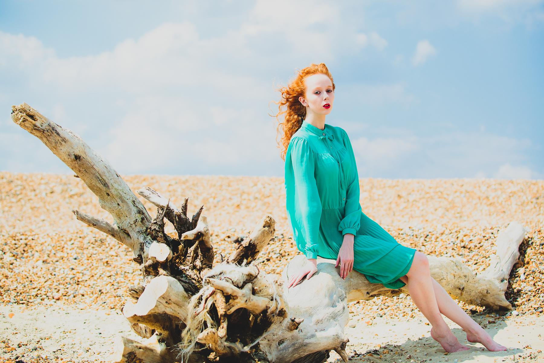 Woman sitting on tree on a beach
