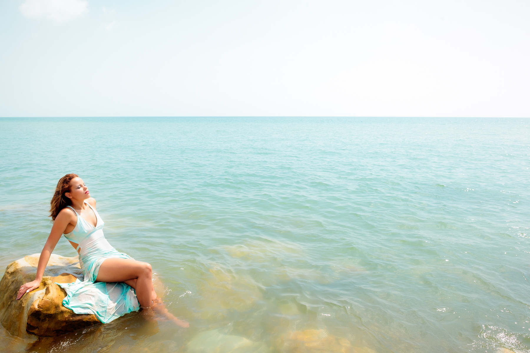 Woman enjoying the sea on a rock
