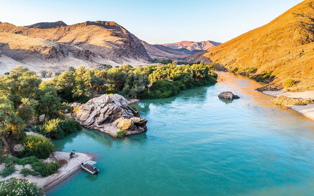 Seen from above, the Kunene looks almost like an oil painting; the beauty is unreal, with trees covering the green banks. The boat belongs to Serra Cafema Camp, the most beautiful lodge on the river  Photo © 2018 Michael Poliza. All rights reserved.  www.michaelpoliza.com