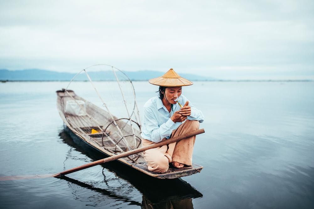 Ein Fischer zündet sich bei seiner Morgentour auf dem Inle-See eine Zigarette an, Myanmar  Photo © 2019 Pie Aerts. All rights reserved.